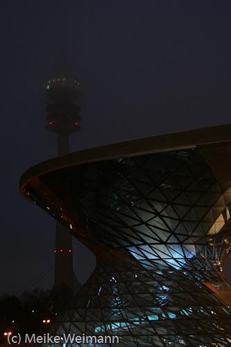 Die BMW-Welt wurde 2008 eröffnet. Dahinter ragt der Olympiaturm auf, der wie das Stadion ebenfalls ein Weltkulturdenkmal ist. Es war leicht nebelig.